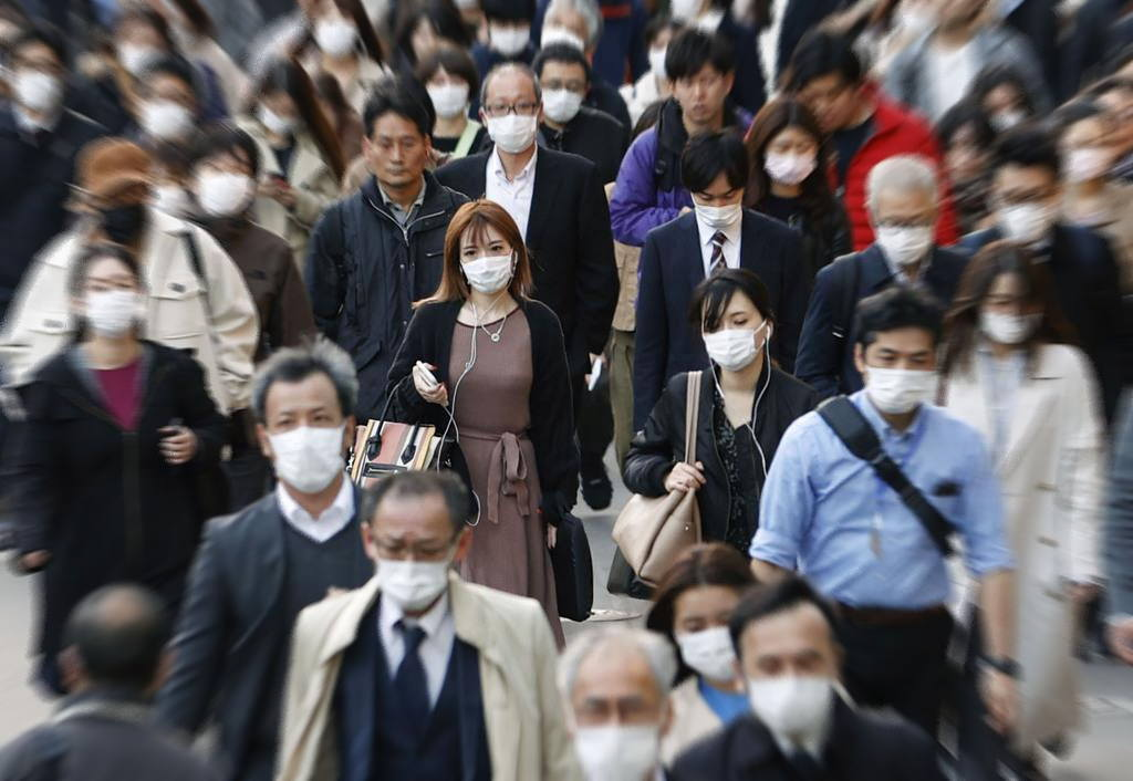 新型コロナウイルス禍でマスクをつけて歩く通勤者